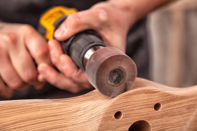 Jovem carpinteiro igual a polimento de tábua de madeira