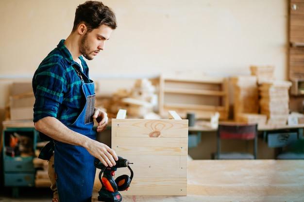 Jovem carpinteiro masculino na oficina, olhando para a câmera