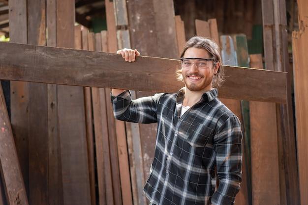 Jovem carpinteiro masculino sorrindo enquanto segura uma prancha de madeira na oficina de carpintaria