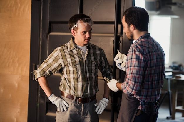 Jovem carpinteiro recebe dinheiro por seu trabalho na oficina de carpintaria