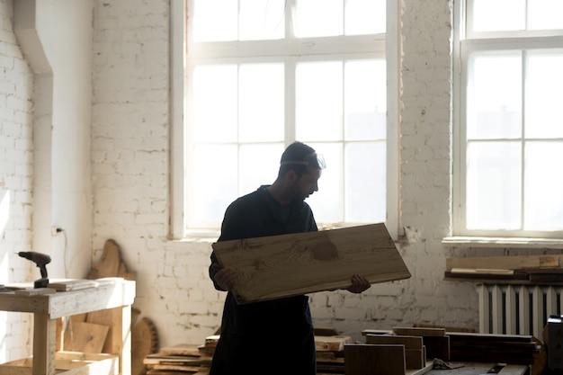 Jovem carpinteiro segurando tábua de madeira, carpintaria em carpintaria interior