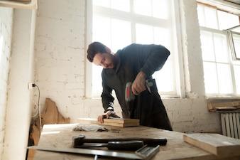 Jovem carpinteiro trabalhando em carpintaria