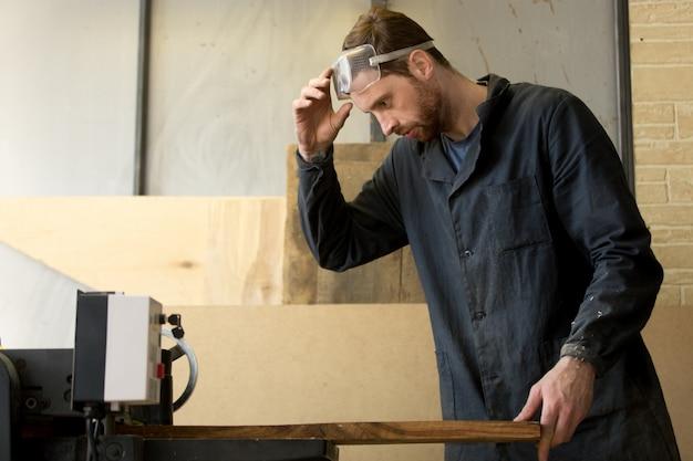 Jovem carpinteiro trabalhando em serração em máquina-ferramenta