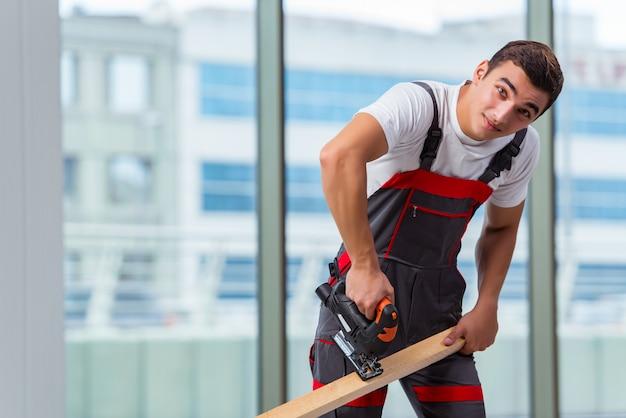 Jovem carpinteiro trabalhando no canteiro de obras