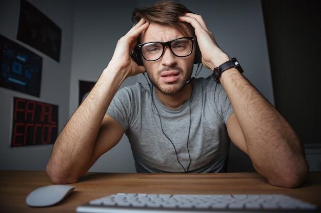 Jovem carrancudo usando fones de ouvido e óculos, sentado com as mãos na cabeça em frente ao computador