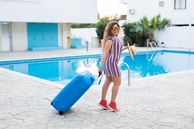 Jovem carregando bagagem azul e chegando ao resort