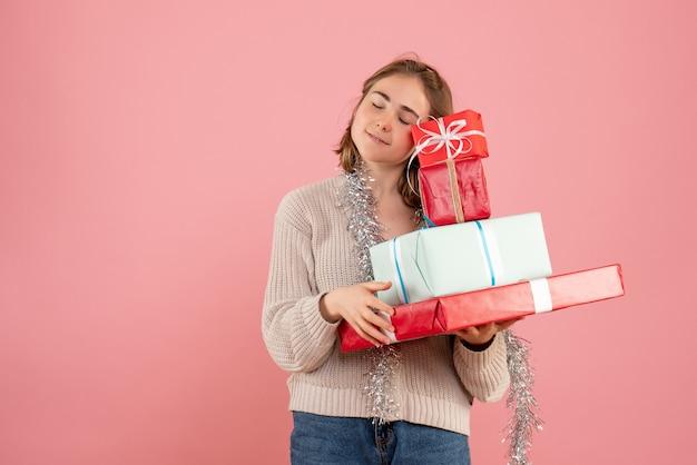 Jovem carregando presentes de natal rosa