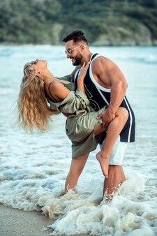 Jovem casal a aninhar-se na praia do mar entre as ondas