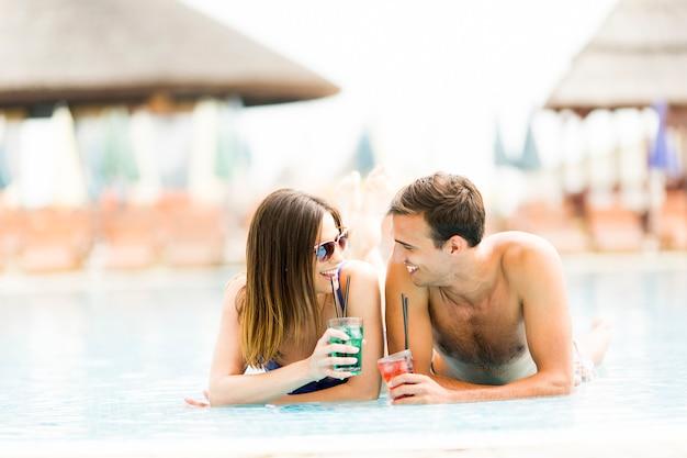 Jovem casal à beira da piscina