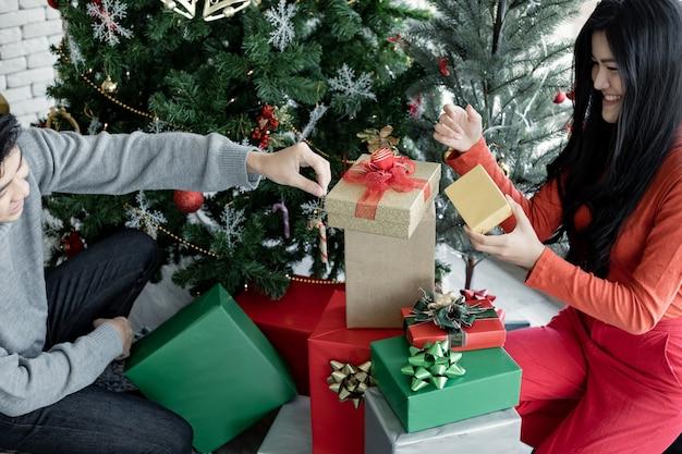 Jovem casal a decorar o natal com caixa de presente da festa de natal. comemorando o ano novo. feliz natal e boas festas.
