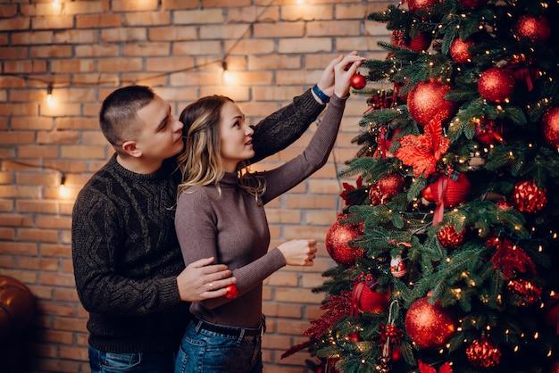 Jovem casal a decorar uma árvore de natal juntos em casa