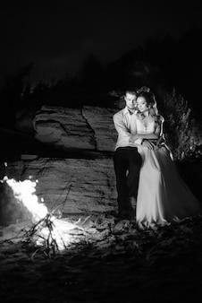 Jovem casal, a noiva e o noivo aquecem ao redor do fogo à noite