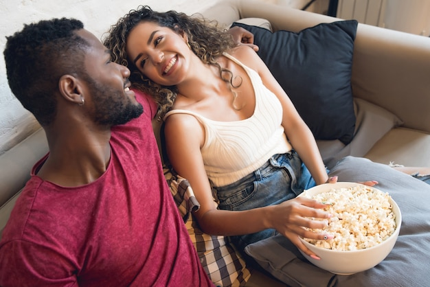 Jovem casal a passar algum tempo juntos e a ver séries de televisão ou filmes enquanto está sentado no sofá em casa.