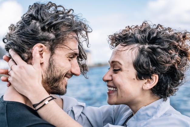 Jovem casal abraçado pelo mar sem foco