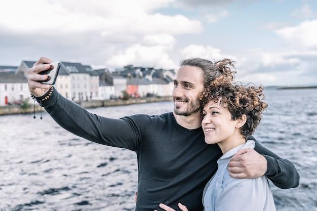 Jovem casal abraçado pelo ombro, fazendo um selfie com o porto e o mar fora de foco