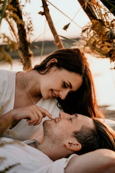 Jovem casal abraçando e beijando na costa do sol. história de amor romântico. menina morena com um vestido leve.
