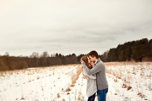 Jovem casal abraçando e se beijando em um prado solitário