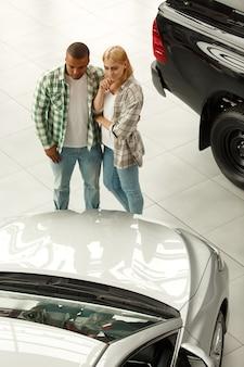 Jovem casal abraçando examinando carros no showroom da concessionária.