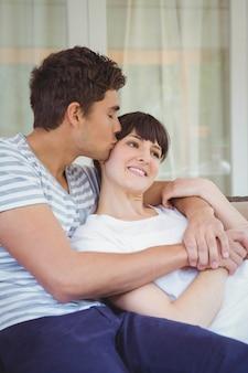 Jovem casal abraçando no sofá na sala de estar