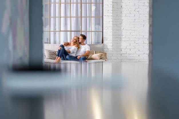 Jovem casal abraçando no sofá