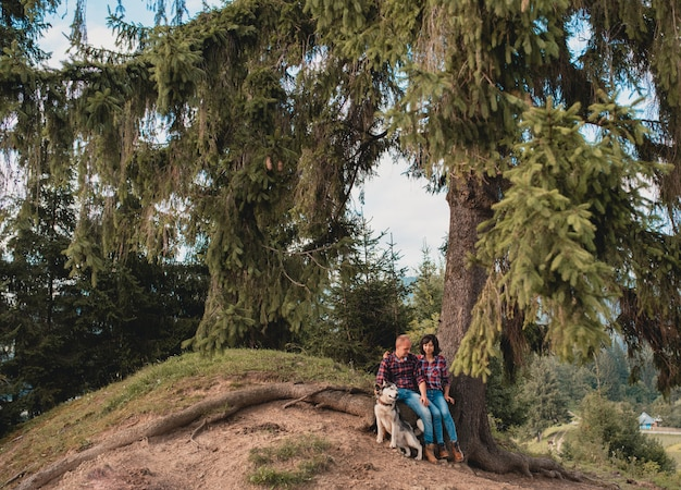 Jovem casal abraçando perto de árvores das montanhas