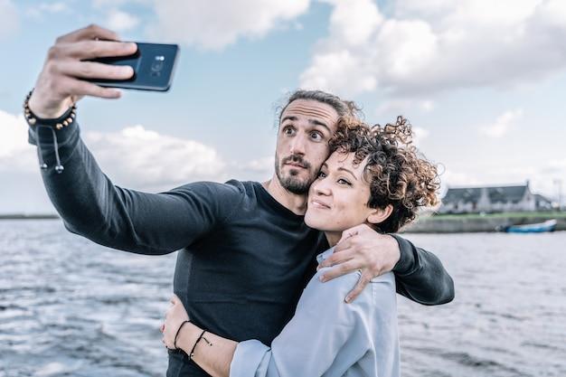 Jovem casal abraçou fazendo um selfie com o porto e o mar fora de foco