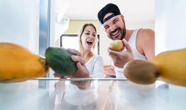 Jovem casal abre a geladeira em casa enquanto escolhe frutas orgânicas para smoothie fresco