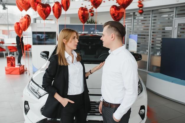 Jovem casal acompanhando um carro em um showroom de carros