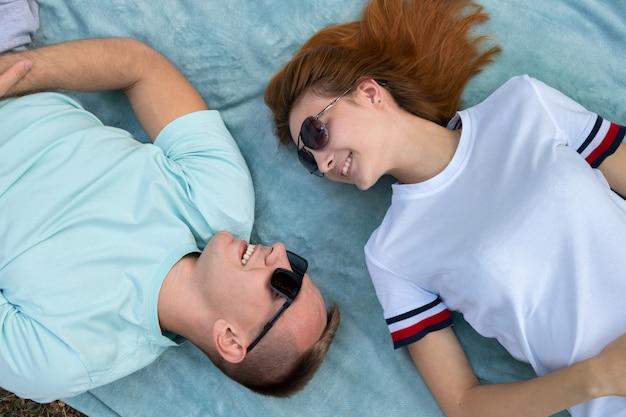 Jovem casal adolescente em óculos de sol deitado juntos no pano azul, desfrutando de relações amorosas.