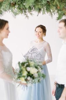 Jovem casal adorável com mestre do discurso da cerimônia de casamento contra o arco de decoração na cerimônia de casamento