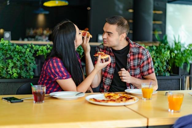 Jovem casal adorável é compartilhar pizza e comê-lo na pizzaria. um cara está alimentando sua garota com um pedaço de pizza em um restaurante.