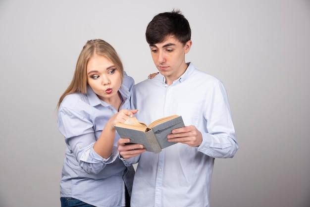 Jovem casal adorável lendo um romance interessante na parede cinza.