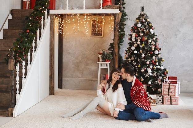 Jovem casal adorável sentado em um tapete e se abraçando perto da árvore de natal decorada