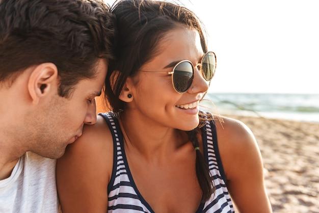 Jovem casal adorável sentado na praia, acampando