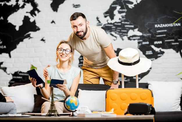 Jovem casal adorável sentado no escritório da agência de viagens se preparando para as férias de verão