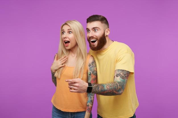 Jovem casal adorável tatuado de olhos abertos olhando surpreso para o lado com a boca aberta enquanto está de pé sobre um fundo roxo em roupas casuais laranja