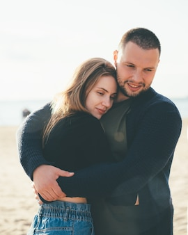 Jovem casal adulto em pé na costa e se abraçando. homem bonito e sorridente abraçando uma mulher