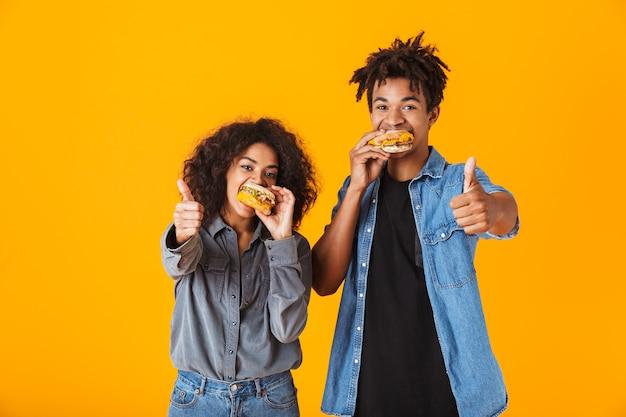 Jovem casal africano alegre, isolado, comendo hambúrgueres com o polegar para cima