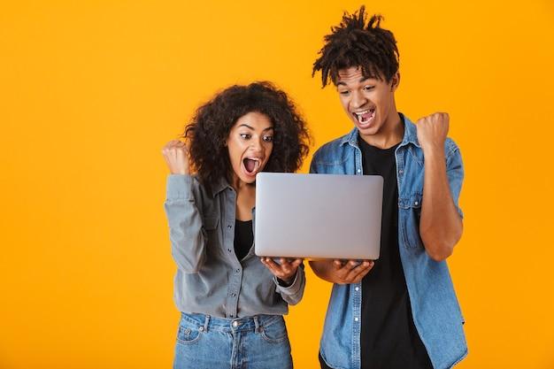 Jovem casal africano alegre, isolado, segurando um laptop, comemorando