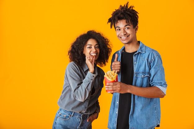 Jovem casal africano alegre parado, isolado, comendo batatas fritas