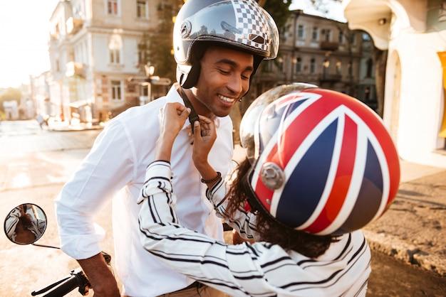 Jovem casal africano em capacetes de moto na rua