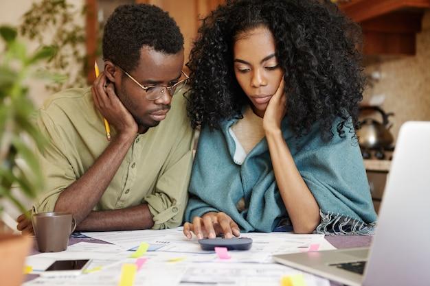 Jovem casal africano estressado não suporta a tensão da crise financeira, parecendo infeliz e frustrado, sentado à mesa da cozinha com calculadora, tentando economizar algum dinheiro cortando despesas domésticas