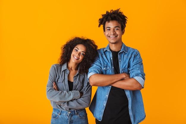 Jovem casal africano feliz vestindo roupas casuais, isolado, braços cruzados