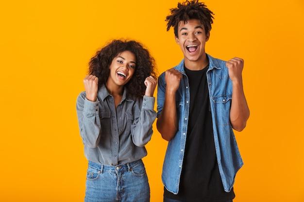 Jovem casal africano feliz, vestindo roupas casuais, isolado, comemorando o sucesso