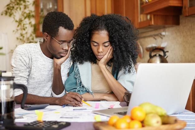 Jovem casal afro-americano chateado, sentindo-se infeliz porque não tem dinheiro para comprar um carro novo