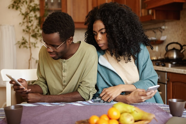 Jovem casal afro-americano usando aparelhos eletrônicos em casa: marido feliz navegando no feed de notícias pelas mídias sociais enquanto sua esposa ciumenta e possessiva espia, tentando ver de quem ele está gostando