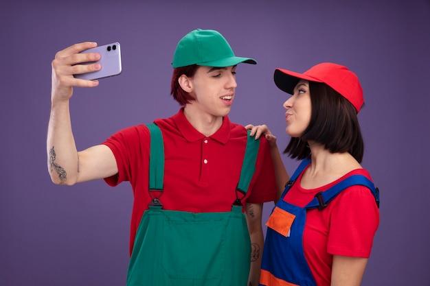 Jovem casal alegre cara feliz garota com uniforme de trabalhador da construção civil e boné tomando selfie juntos, olhando uma para a outra garota segurando o ombro do cara isolado na parede roxa
