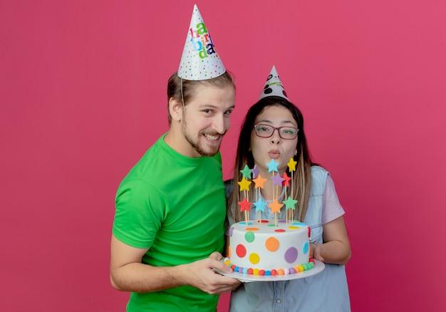 Jovem casal alegre com chapéu de festa segurando um bolo de aniversário, parecendo isolado na parede rosa