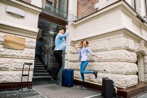Jovem casal alegre com malas pulando e dando cinco, se divertindo, antes de chegar ao hotel.