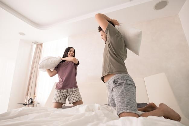 Jovem casal alegre com travesseiros, rindo enquanto se diverte em uma grande cama de casal na manhã de fim de semana, após dormir e tomar café da manhã